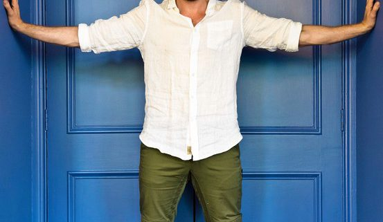 Richard Armitage against blue door with his arms stretched